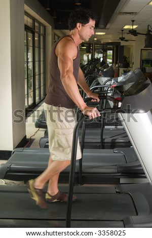 Man working out on a treadmill in a fitness center.  His feet are blurred from the walking motion. - stock photo
