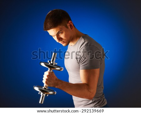 Man working out with dumbbells on blue background - stock photo