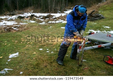 Man working outdoor grinding steel on a trailer - stock photo