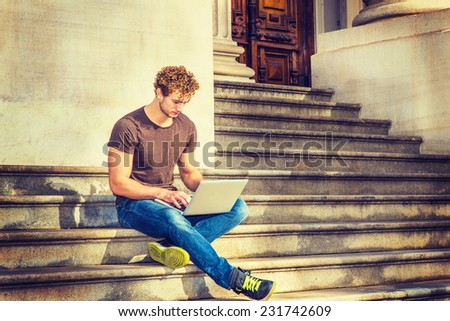 Man Working Outside. Wearing brown T shirt, blue jeans, black sneakers, a young sexy guy with curly hair is sitting on stairs outside office, crossing legs, looking down, typing on laptop computer. - stock photo