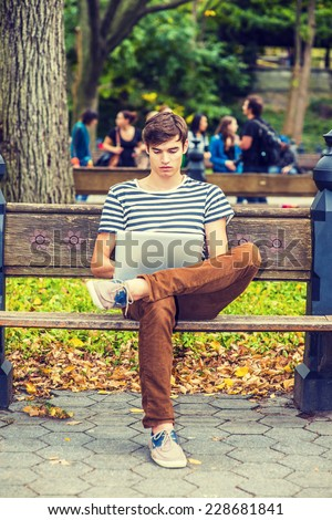 Man Working Outside. Wearing striped T shirt, brown corduroy pants, sneakers, a young handsome guy is sitting on bench on a park, crossing legs, looking down, reading on laptop computer.  - stock photo