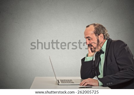 Man working reading something on his laptop computer  - stock photo
