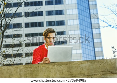Man working remotely. Young blonde graduate student, wearing red sweater, frowned, working on laptop computer on the top of wall on school campus. Instagram filtered effect. - stock photo