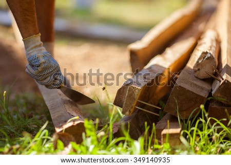 Man working, remove metal nails from piece of timber - stock photo