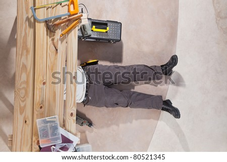 Man working under the wooden plank with tools