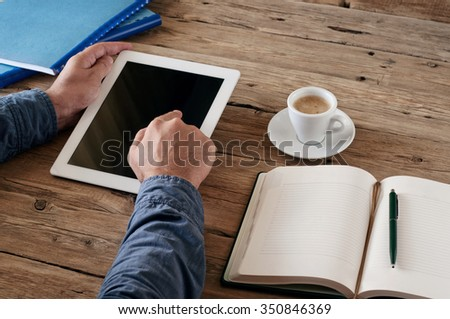Man working with a tablet computer on a wooden table. Top view