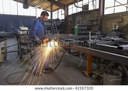 man working with angle grinder on steel construction at industrial workshop