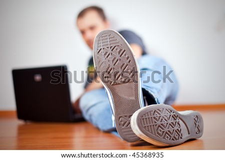 man working with computer on wooden floor.  view on outsole