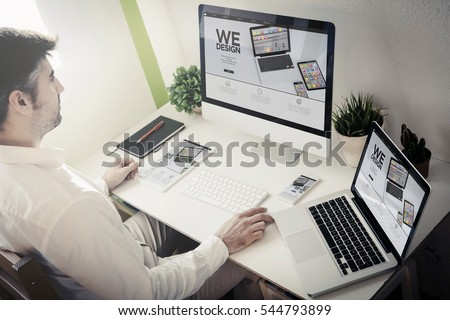 man working with devices with responsive website. All screen graphics are made up.