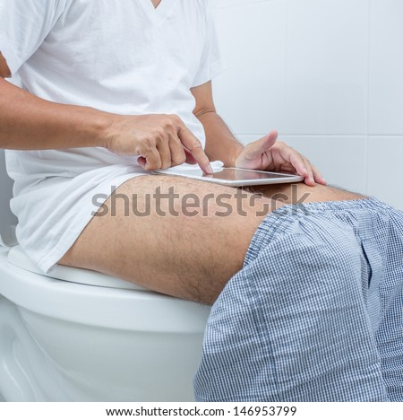 man working with digital tablet while  sitting on the toilet - stock photo