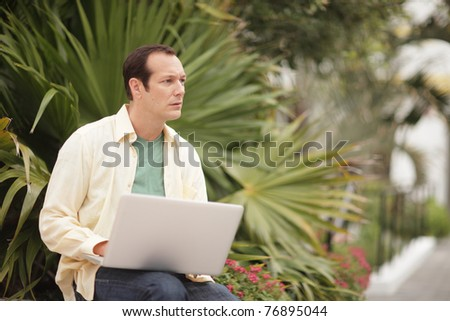 Man working with his notebook computer - stock photo