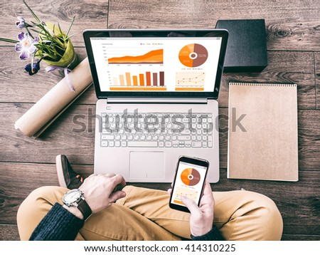 Man working with laptop and smartphone with financial report charts - stock photo
