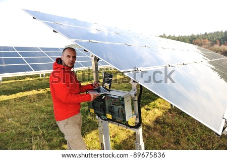 Man working with laptop at solar panels field - stock photo