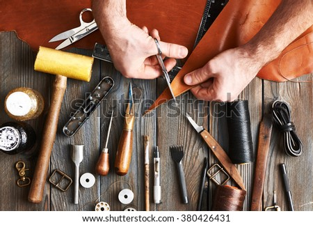 Man working with leather using crafting DIY tools  - stock photo