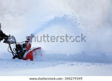 man working with snow blower after winter storm in city - stock photo