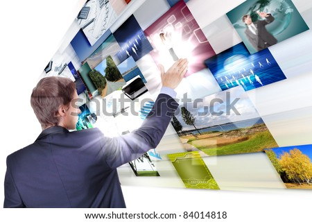 Man working with vurtial screens with different images - stock photo