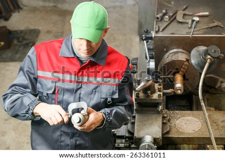 Man works in a lathe in a workshop.Worker measures the detail - stock photo