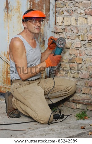 Man works with angular electric grinder. Ukraine