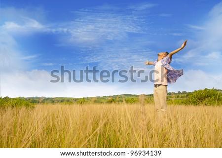 Man worshiping god shot at yellow grass - stock photo