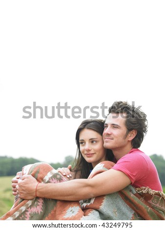 Man wraps arms around woman as they sit together outdoors. Vertical. - stock photo