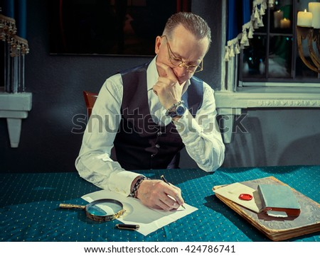 Man writes a letter to a pen at the table