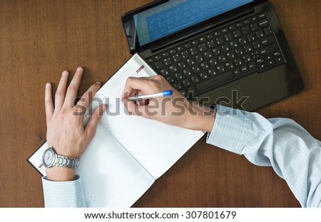 Man writes a note in his diary after an analysis of information on the computer. - stock photo
