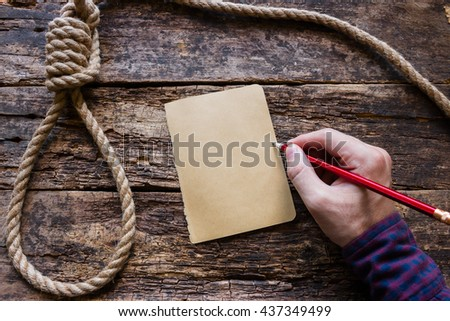 man writes a suicide note - stock photo