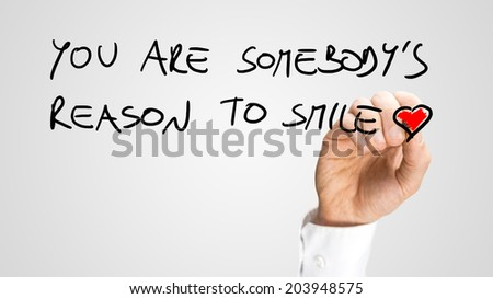 Man writing a beautiful motivational or spiritual message - You are somebody's reason to smile - with a red heart at the end on a virtual interface over white with copyspace. - stock photo