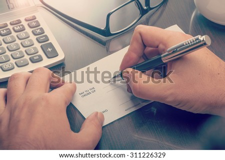 Man writing a payment check at the table with calculator and glasses - stock photo