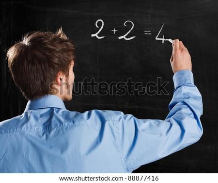 Man writing a simple formula on a blackboard - stock photo