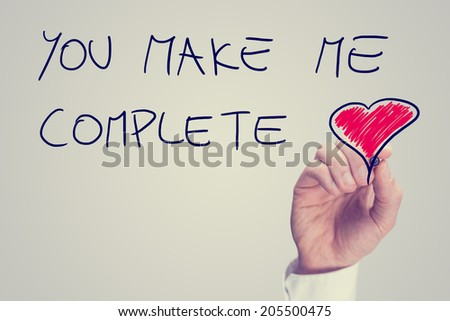 Man writing an inspirational message of love on a virtual interface with the words - You Make Me Complete - with a red heart and copyspace, retro effect faded look. - stock photo