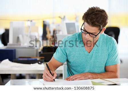 Man Writing At Desk In Busy Creative Office - stock photo