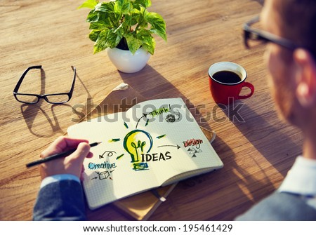 Man Writing Idea Concepts on His Note  - stock photo
