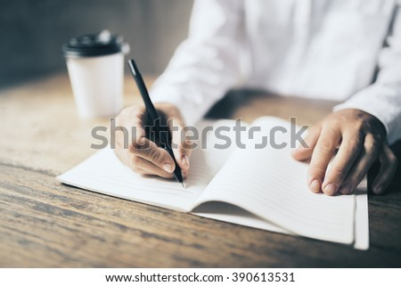 Man writing in blank diary and paper coffee cup on wooden table - stock photo