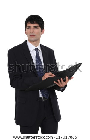 Man writing in business document folder