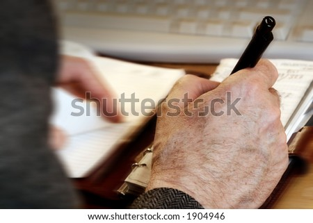 man writing in his agenda, computer keyboard in the background - stock photo