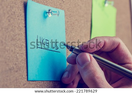 Man writing - Like Us - on a blue note notice board in a request for followers on social media sites and networks. - stock photo