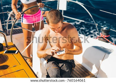 Man writing messages on smart phone, couple on yacht