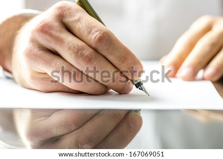 Man writing on a blank paper with ink pen. - stock photo