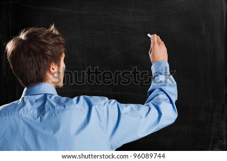Man writing on a empty blackboard. You can add your own text