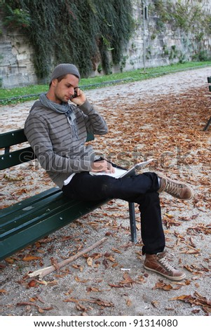 Man writing on notebook and on the Phone on a Bench Outdoors - stock photo