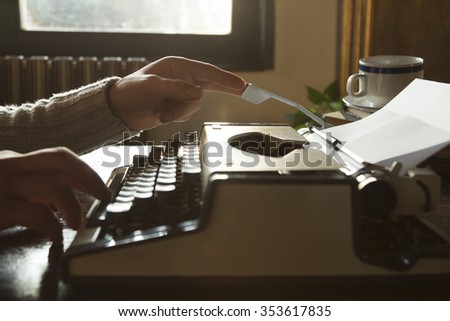 Man writing on old typewriter. - stock photo