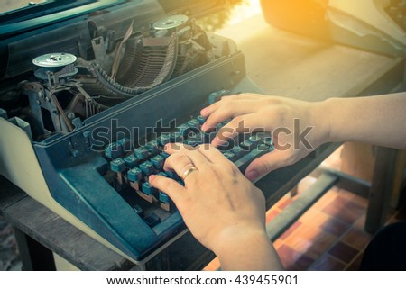 Man writing on old typewriter,vintage color,selective focus. - stock photo