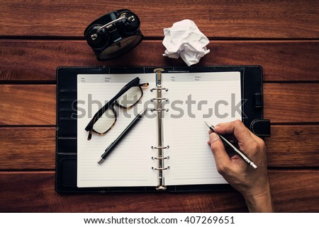 Man writing on personal organizer over wooden table background, flat lay, workplace and business concept - stock photo