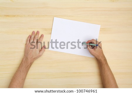 man writing on the paper, top view - stock photo