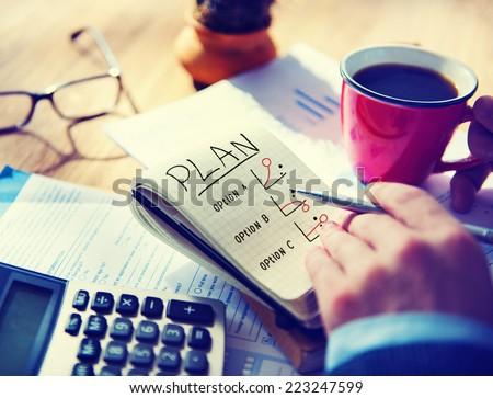 Man Writing Plan in Note Pad - stock photo