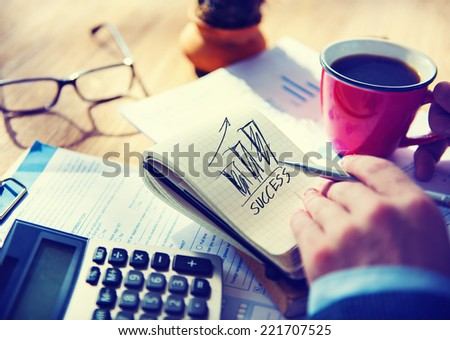 Man Writing Success in Note Pad - stock photo