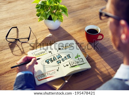 Man Writing Team Work Concepts on His Note - stock photo