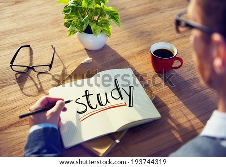 Man Writing the Text Study on His Note - stock photo