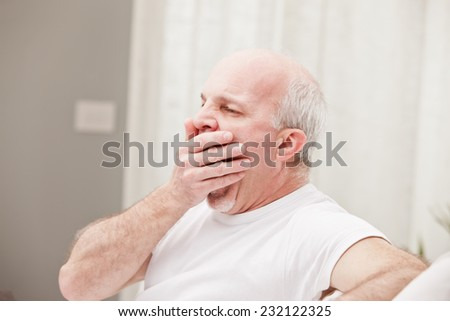 man yawning and going asleep in his white living room - stock photo